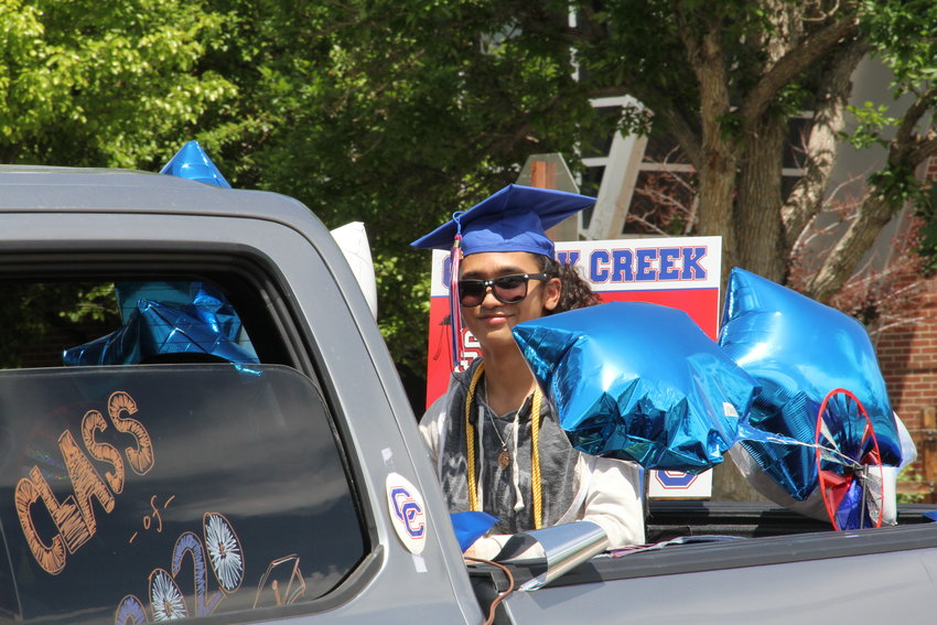 Student Ray Michael rides in a truck bed through the parade.