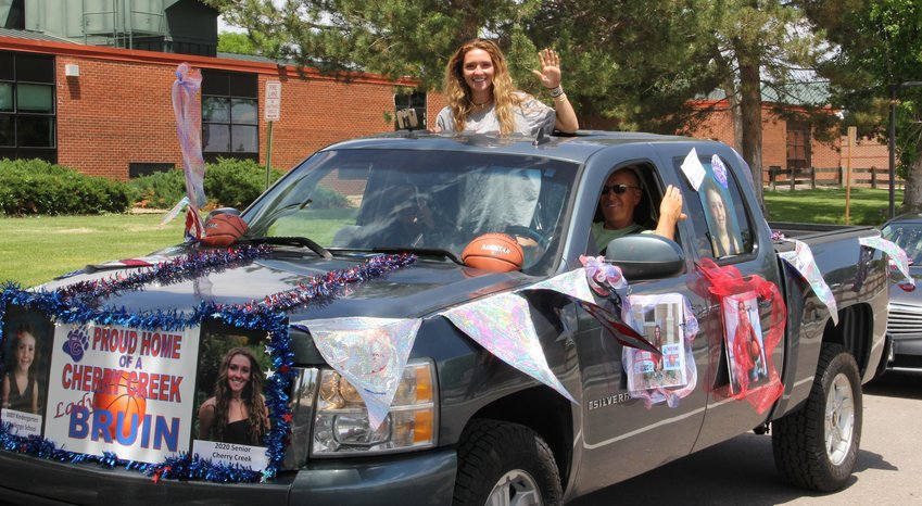 Jana Van Gytenbeek waves from the bed of a truck bearing lots of memorabilia, including what appear to be photos of her as a young child and, in the back, posters showing her as a girls basketball player and prom queen.