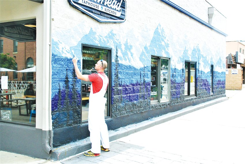 Jesse Crock adds paint to his mural on the Miners Alley side of Trailhouse Taphouse & Kitchen in Golden.
