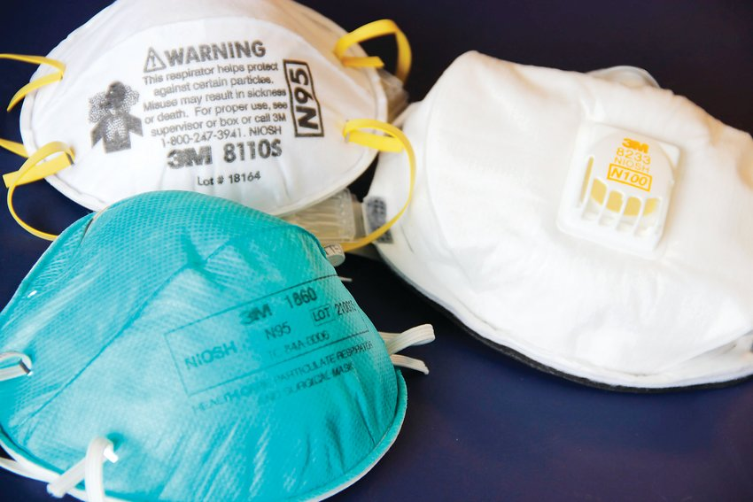 Two N95-type face masks, or respirators, at left. On right, a third respirator, an N100-type mask.