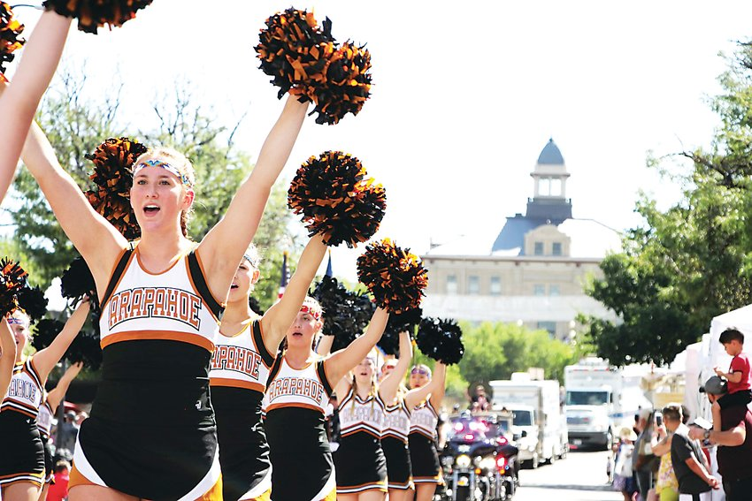 Arapahoe High School cheerleaders march down Main Street during the 2019 Western Welcome Week Grand Parade. This year's parade has been canceled over concerns about spreading COVID-19.