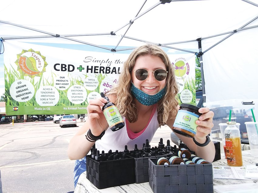 Merisa Trujillo, 20, stands at her booth for Dragonfly Botanicals and Taspen's Organics June 10 at the Centennial Farmers Market. The Lakewood resident has worked farmers markets around the Denver metro area.
