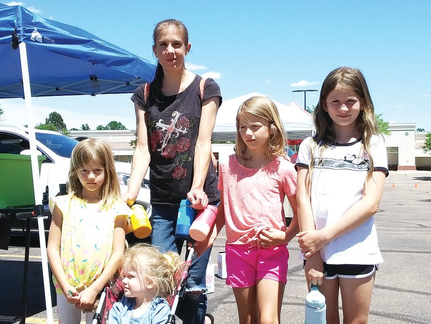 "Lexie Satkowski, a 31-year-old Centennial resident, walks with, from left: Eve, 5; Tetra, 3; Sonja, 7; and Una, 9. Satkowski said of the Centennial Farmers Market: ""It has everything you need."""