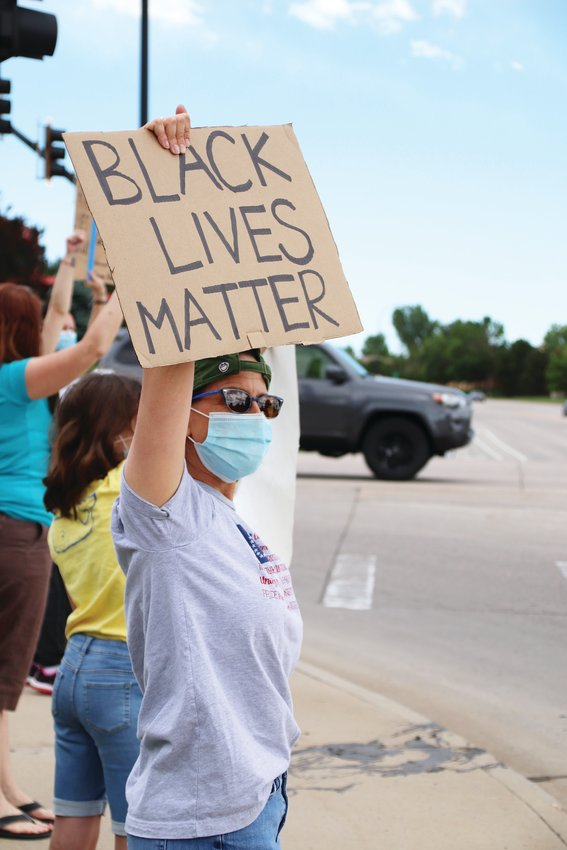 A masked Highlands Ranch resident looks out at traffic on Lucent Boulevard as she holds a Black Lives Matter sign over her head June 8.