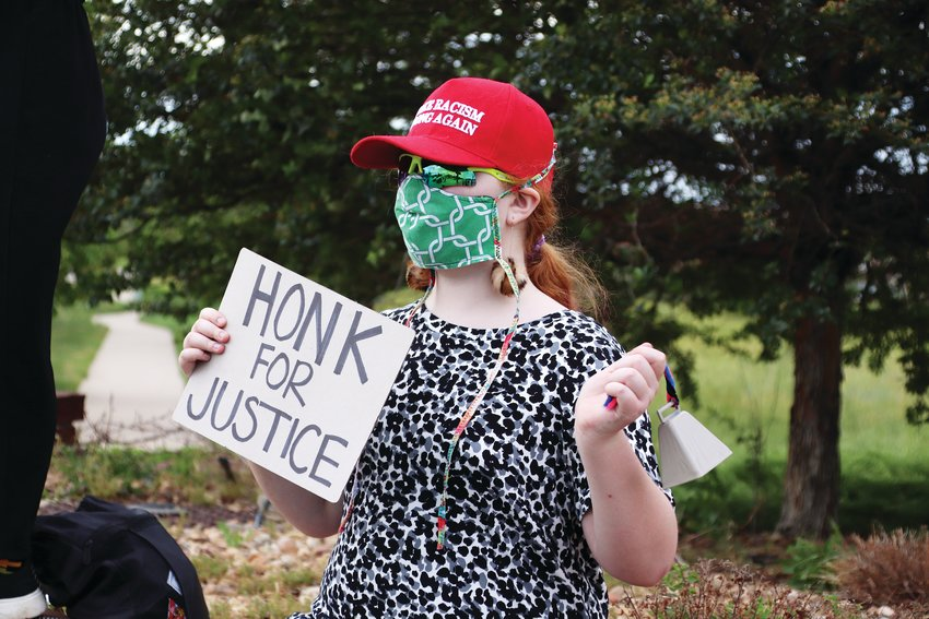 "Highlands Ranch resident Kaia Watson, 10, wears a red ""Make Racism Wrong Again"" hat and carried a ""Honk For Justice"" sign at an intersection in Highlands Ranch June 8. She also carried a cow bell that she rang throughout the protest."