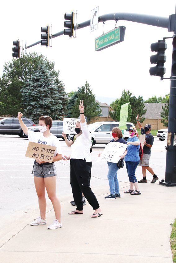 "Protesters carrying signs with messages like ""Black Lives Matter"" and ""the time to act is now"" stand along the corner of Lucent Boulevard and Highlands Ranch Parkway."