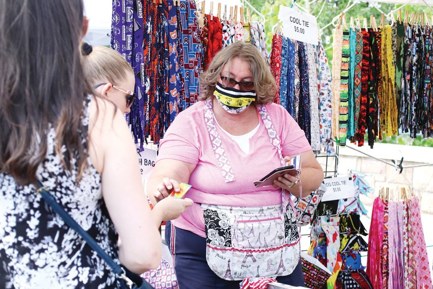 Pat Schuessler rings up a customer at her Everything Fab stand, where she sells crafted cool ties, trash bags and collapsible dog bowls.