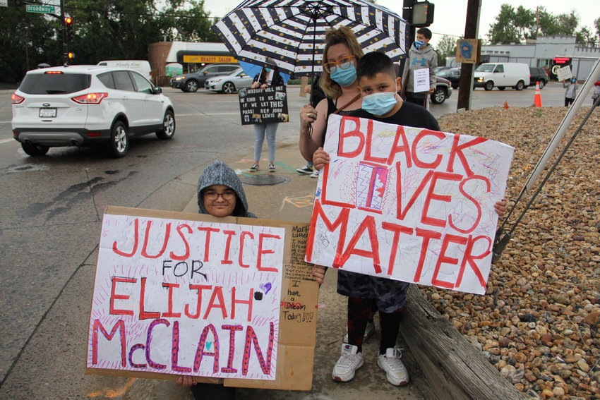 "Khloe Lillyblad, 11, left, and Aaziah Monroy, 10, hold signs that say ""Black lives matter"" and ""Justice for Elijah McClain"" at a protest against police treatment of Black Americans along the Centennial-Littleton border. McClain, a 23-year-old Black man, died in August following an encounter with Aurora police."
