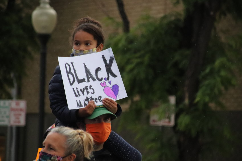A girl carries a sign along the route of the Black Lives Matter Solidarity Walk in Littleton on June 18.