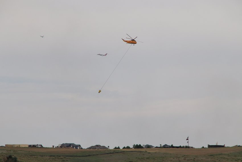 A firefighting helicopter and other aircraft near the Chatridge 2 fire burning in Douglas County on June 29, 2020.