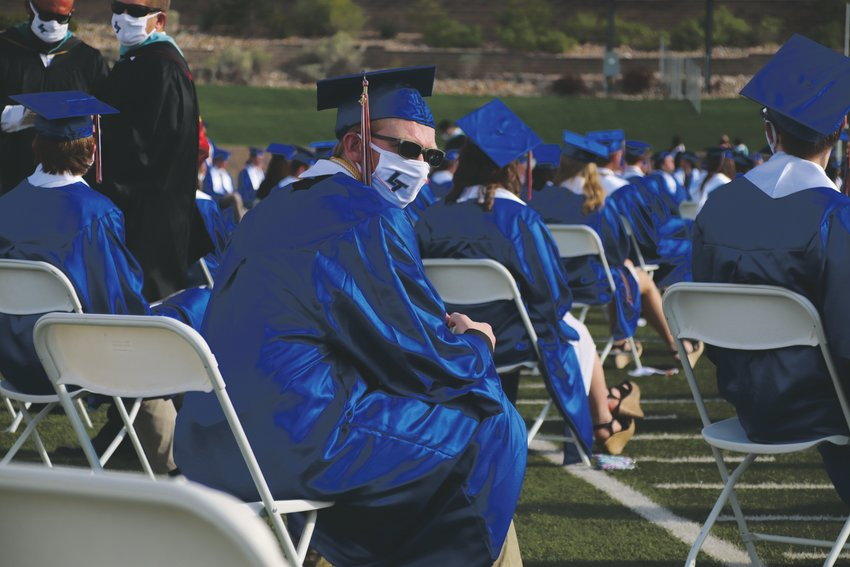 A Legend High School senior awaits the start of the June 25 graduation ceremony while wearing a face mask. Masks were not required at the outdoor event.