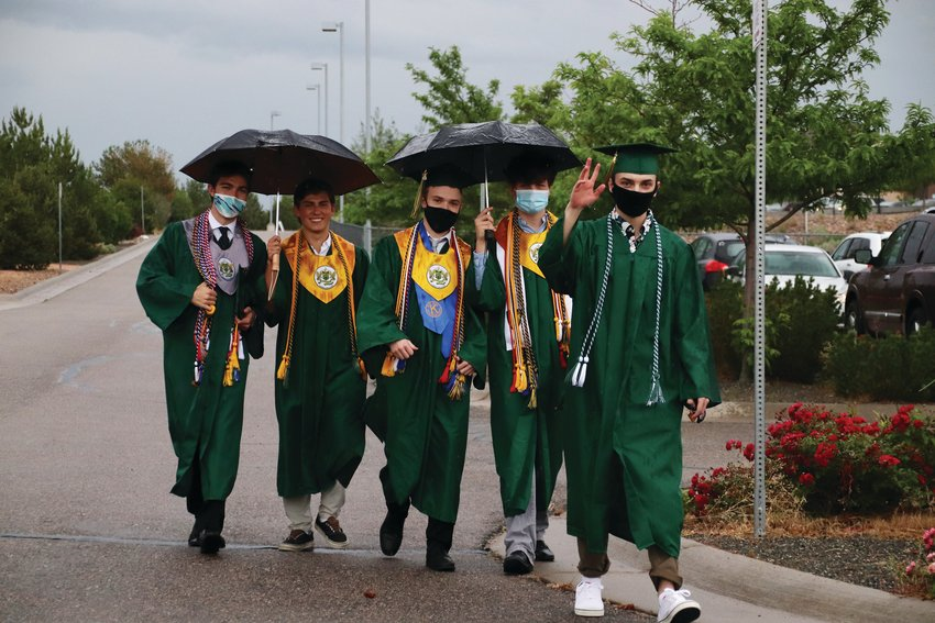 A group of Mountain Vista High School seniors walk through the parking lot at EchoPark Stadium in Parker after their graduation ceremony was delayed by lightning.