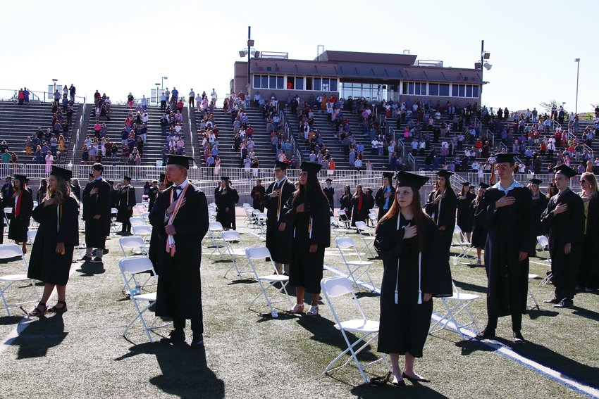 Castle View High School students stand for the national anthem during their graduation ceremony June 26. Students and their guests were all spaced 6 feet apart during the event.