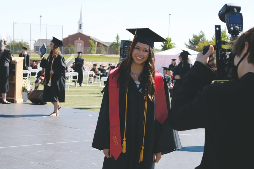 A Castle View graduate poses for a photographer after walking across the graduation stage June 26.
