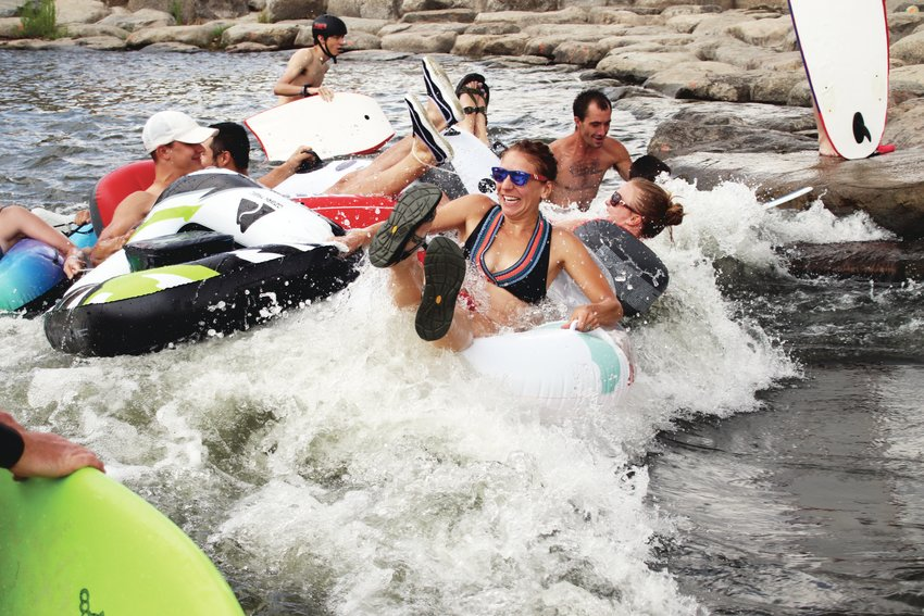 A flotilla of tubers crashes through a boat chute at River Run Park in Englewood.