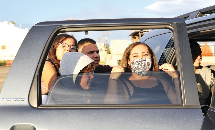 Vantage Point High School graduate Cheyenne Aragon, right, finishes adjusting her face mask, during the Northglenn alternative high school's drive-in graduation.
