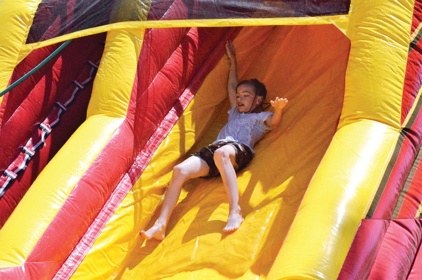 Dax Schulte, 9, of Westminster launches down the chute of the water slide at Camp Kind, located at the Chabad of NW Metro Denver, June 23.