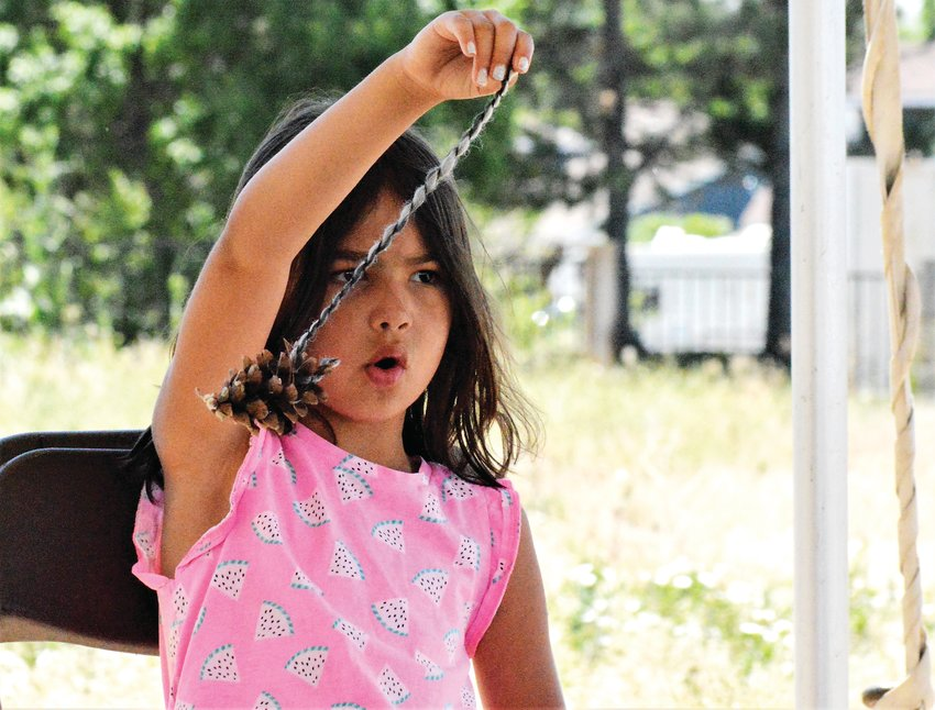 Adalina Garcia, 5, checks on a pine cone she'll use to make a treat for rabbits, part of the day's activities June 23 at Camp Kind in Westminster. The pine cone will be filled with parsley for rabbits at the Colorado House Rabbit Society.