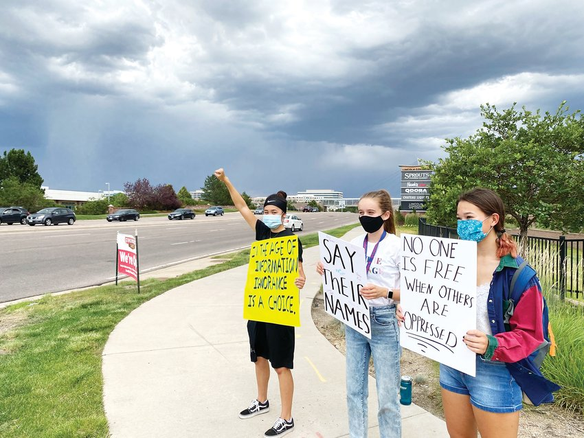 From left, Lexi Bauer, Eileen Kennedy and Maddie Provost stand on the corner of Commons Street and Lincoln Avenue in Lone Tree July 4 in support of the Black Lives Matter movement.