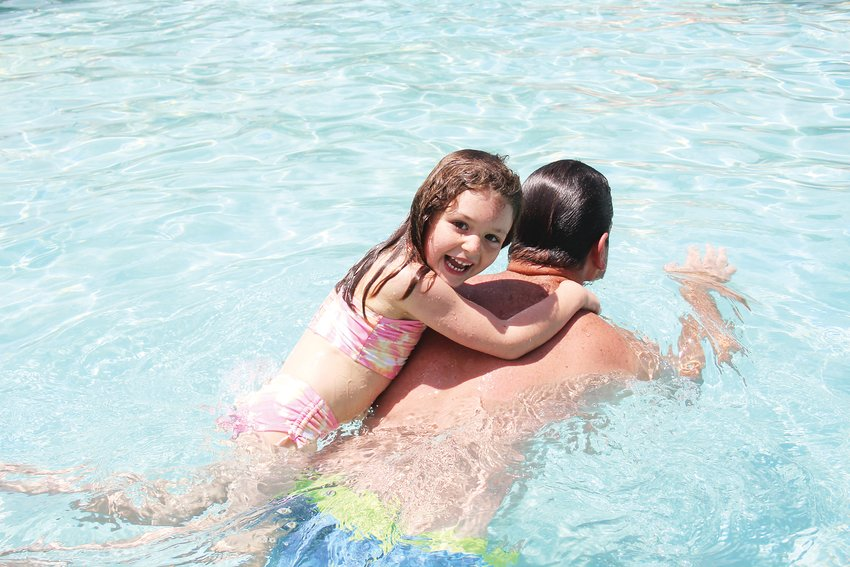 Colette Daniels holds onto her father Ryan Daniels' back at Pirates Cove Water Park on July 2. The water park and the Englewood Recreation Center are the Englewood Parks, Recreation and Library Department's top revenue strengths.