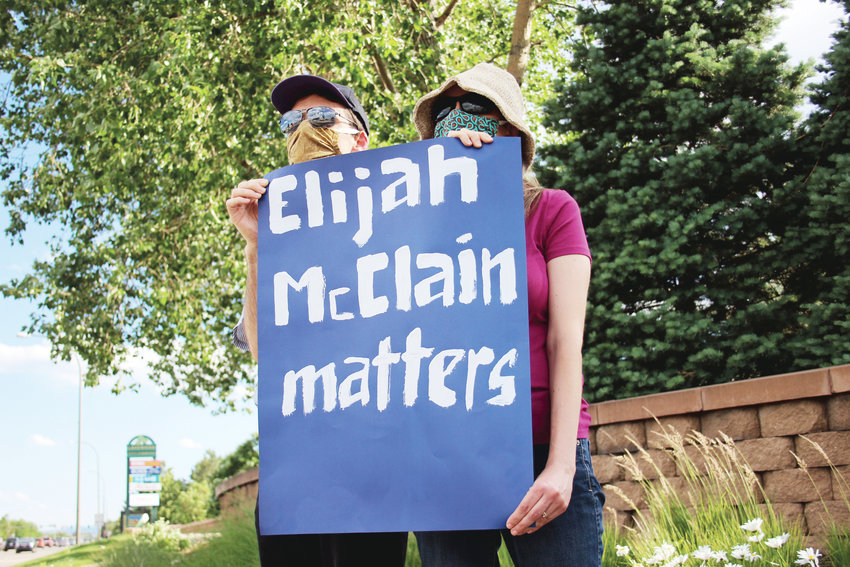 A man who declined to give his name and Diane Reese hold a Elijah McClain sign. McClain died after a confrontation with Aurora Police last August.