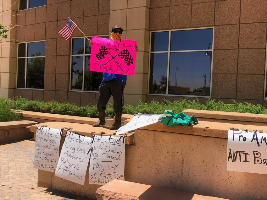 An opponent of recent racing events at Bandimere Speedway protests outside the Jefferson County Building on March 8.