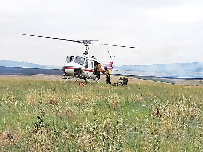 A helicopter lands near Chatfield Reservoir to assist fire crews in a June 29 blaze at the south end of the reservoir.