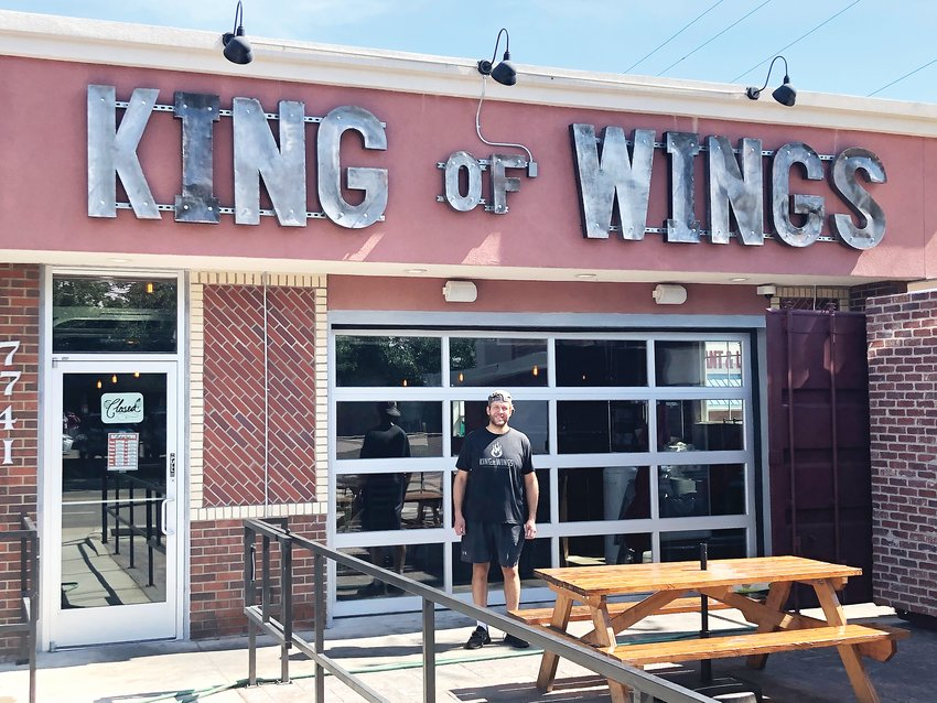 Eddie Renshaw stands outside the King of Wings restaurant. Renshaw owns the new restaurant with his partner, Evan Pierce.