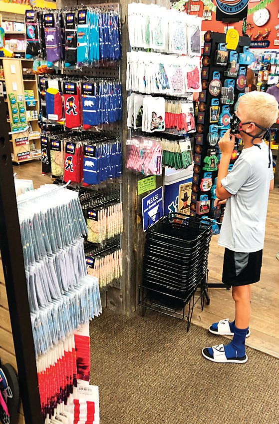 A boy looks at the face masks on sale at Golden Goods.