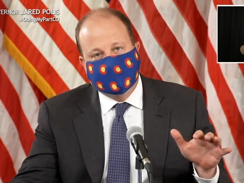 Colorado Gov. Jared Polis in July 2020 announcing the statewide order requiring those over age 10 to wear masks indoors. An interpreter for the hearing impaired appears at upper right.