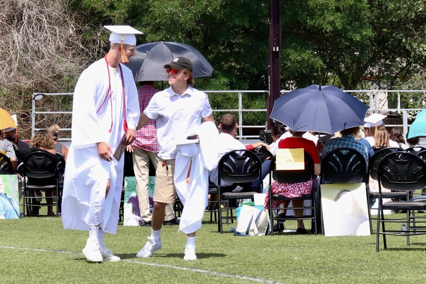 A graduate is congratulated by a friend after receiving his diploma.