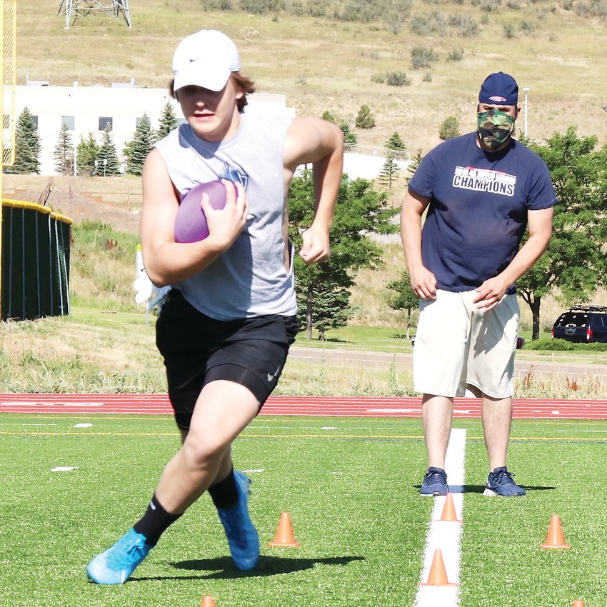 During Phase 3 of Jeffco's phase-in of athletics and activities, a football player at Dakota Ridge High School runs through a drill individually as his coach wears a mask.