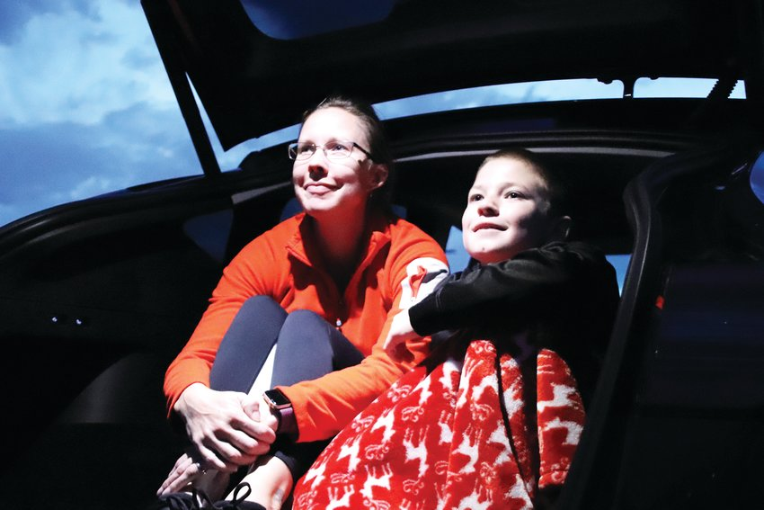 Suzi Losasso, 39, left, and James Losasso, 11, watch a drive-in movie put on by the City of Centennial.