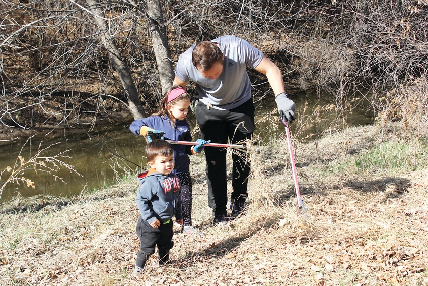 In this 2019 photo, Michael Mersmann and his two children, Ellie and Dominic, are seen picking up trash next to the High Line Canal. Mersmann said the cleanup was an opportunity to teach his children about volunteering in the community.