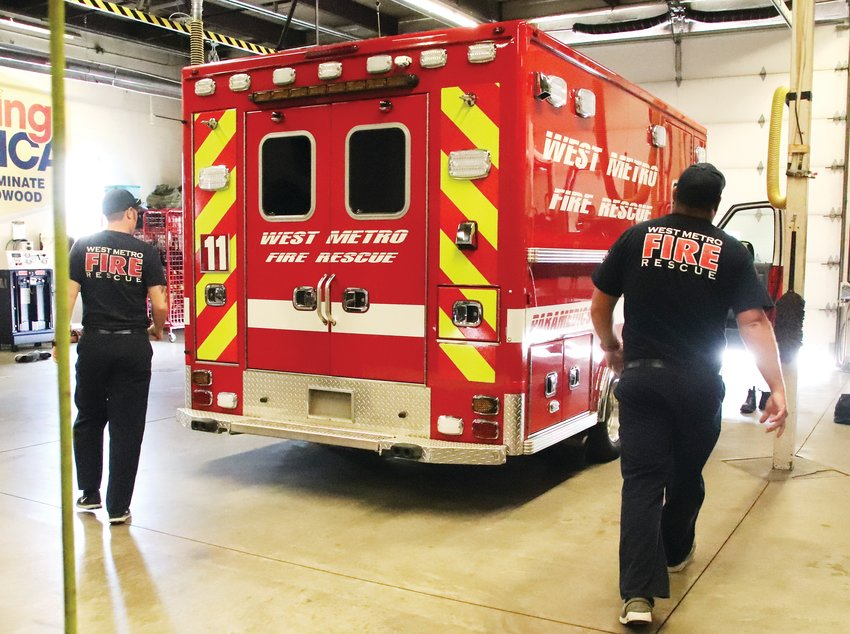 Firefighters and paramedics Chris Marvin, left, and Tyler Finley prepare to climb into a West Metro Fire Rescue ambulance to respond to an emergency call on July 23.