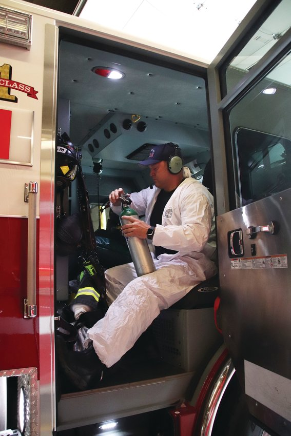 Firefighter and paramedic Nick Bourne holds a medical oxygen tank while wearing personal protective equipment in the back of a West Metro Fire Rescue fire engine moments before the truck departed from Station 1 on July 23.