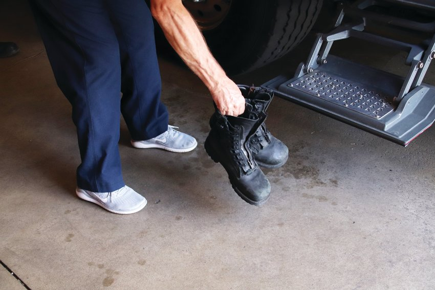 Lt. Brian Worth of West Metro Fire Rescue grabs his boots after returning from an emergency call July 23.