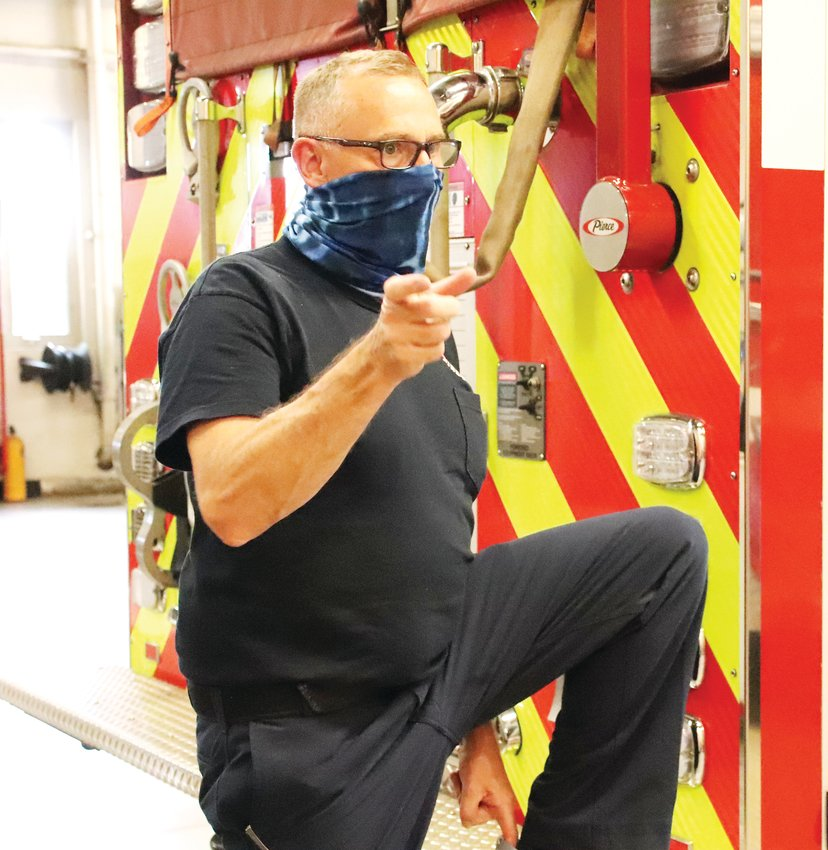 Lt. Brian Worth of West Metro Fire Rescue stands with his foot on the back of a fire engine in Station 1 of West Metro Fire Rescue July 23.