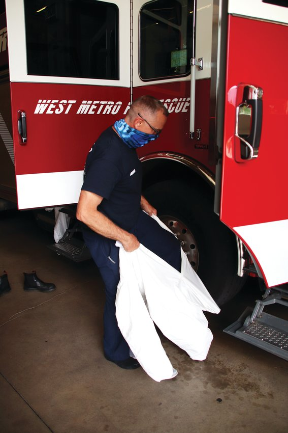 Lt. Brian Worth of West Metro Fire Rescue pulls on a gown moments before climbing into a fire engine July 23. The team was called to respond to a woman in labor, he said.