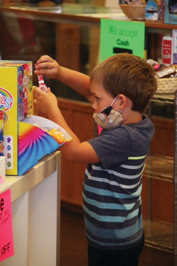 Willard Bone, 4, picks up a watch at Timbuk Toys in Highlands Ranch July 23.