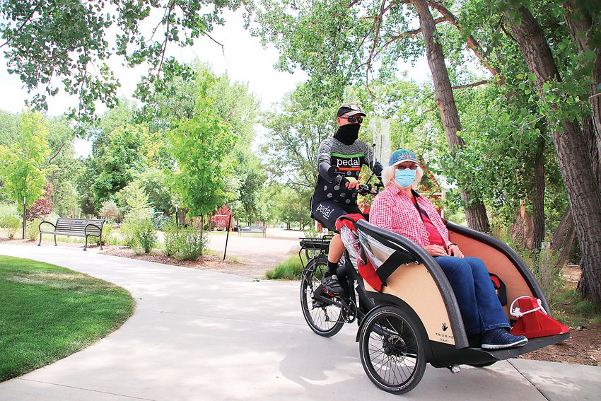 "Former Littleton Mayor Phil Cernanec, left, gives Bonnie Douglas a ""trishaw"" ride through Hudson Gardens on July 28. Cernanec helped found Littleton's chapter of Cycling Without Age, which takes seniors on rides around town."