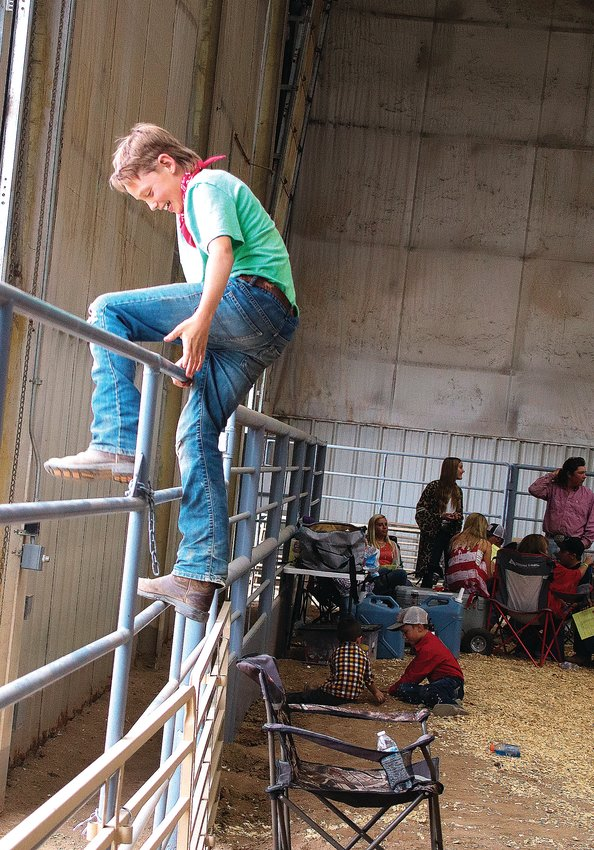 TJ Surry, 11, hops over a fence at the July 31 livestock sale in Douglas County. Surry had already brought his livestock to sell the weekend prior but attended the show to support his younger sister, who was selling a pig.