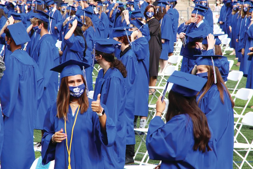 A student, bottom left, turns to give the thumbs-up sign as graduates stand for the traditional moving of the tassels on their caps July 27 at Grandview High School's graduation ceremony.