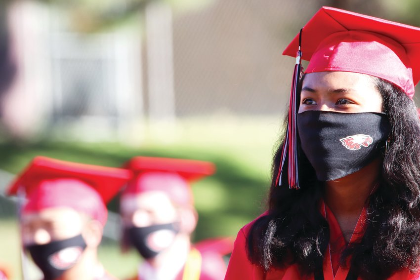 A student sits in the crowd, wearing an Eaglecrest-themed face mask. Many students wore the same type of mask bearing their school's logo at graduation.