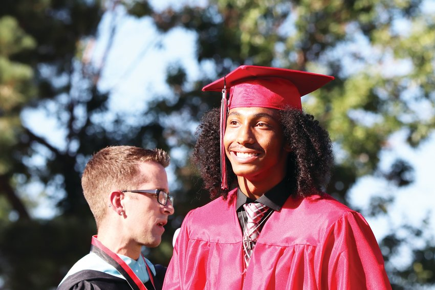 Students walk in front of the crowd after their names are called at Eaglecrest High School's graduation ceremony July 31 at Cherry Creek High School's Stutler Bowl stadium.