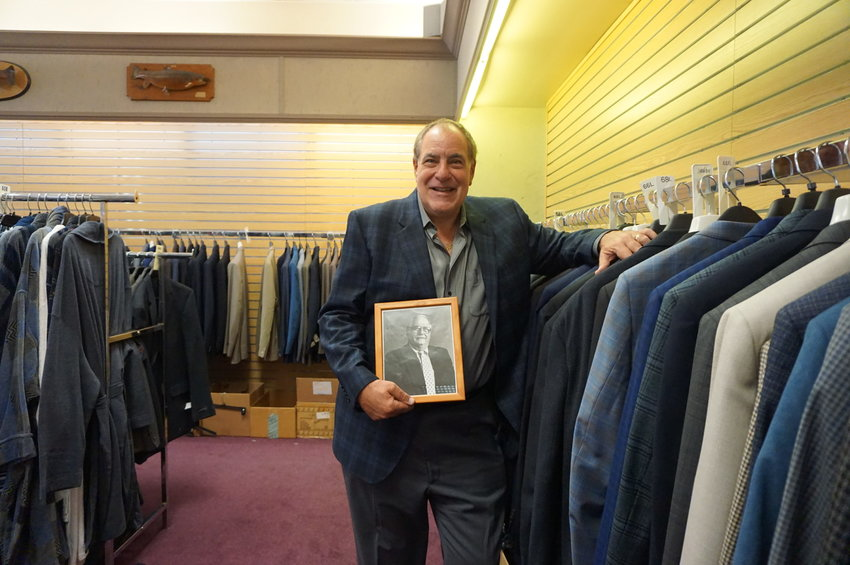 Kaufman's owner Sam Kaufman with a photo of his father, Fred, who opened the tall and big clothing store in 1958.