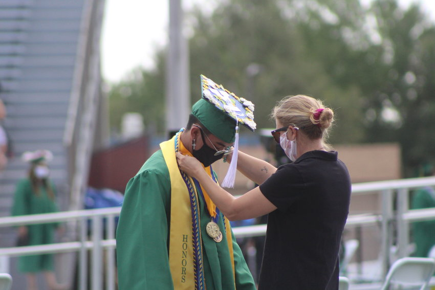 A woman helps a graduate look his best before he took a photo with his diploma.