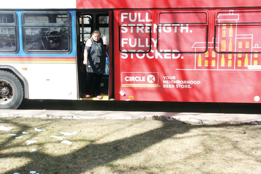 In a February file photo, a woman exits an RTD 16L bus at the 10th and Washington stop in downtown Golden.