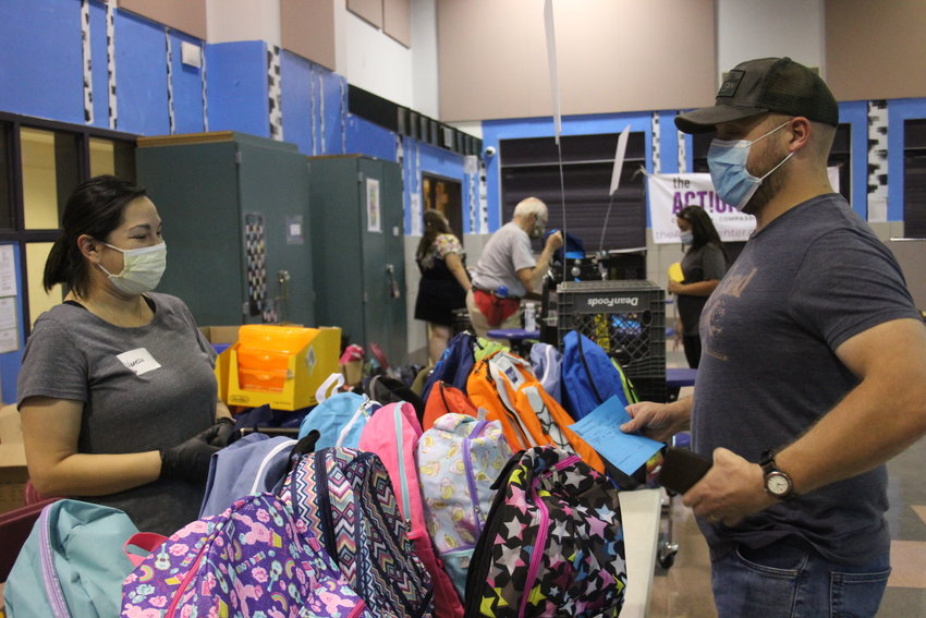 Vanessa Diaz assists Greg Hoflin with selecting a backpack. Only one person per household was allowed into the school supply distribution site to prevent the spread of the coronavirus.