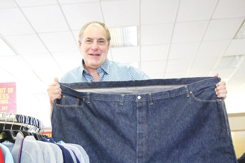 Sam Kaufman, owner of Kaufman's Tall and Big Shop in Englewood, holds a pair of size 76 jeans at his store. After 62 years of being in Englewood, Kaufman's Tall and Big Shop is planning to close its doors at the end of October.